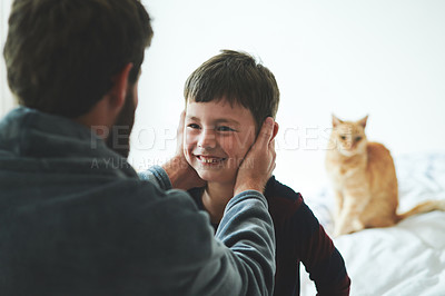 Buy stock photo Shot of a young man helping his adorable son get dressed in the morning at home