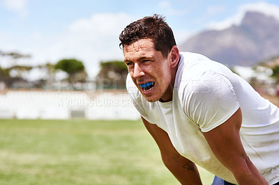 Buy stock photo Shot of a young man wearing a gum guard while playing a game of rugby