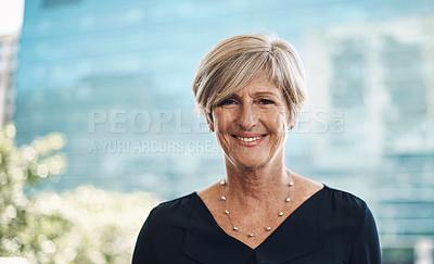 Buy stock photo Portrait of a confident mature businesswoman against a city background