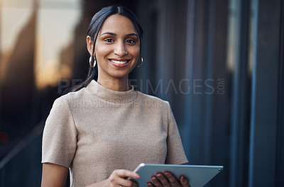 Buy stock photo Cropped portrait of an attractive young businesswoman using her tablet while working in the office