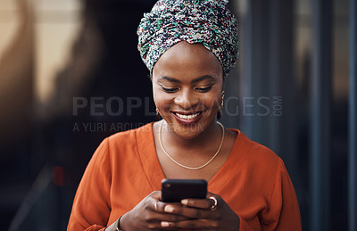 Buy stock photo Cropped shot of an attractive businesswoman sending a text while standing in the office