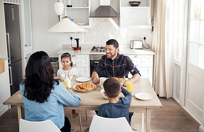 Buy stock photo Shot of a young family sitting down together to share a delicious breakfast at home