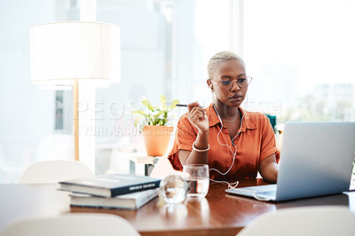 Buy stock photo Shot of a young businesswoman wearing earphones while working on a laptop in an office