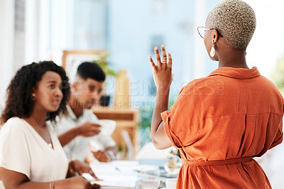 Buy stock photo Rearview shot of a young businesswoman giving a presentation to her colleagues in an office
