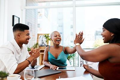 Buy stock photo Shot of a group of businesspeople giving each other high five during a meeting in a modern office