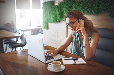 Buy stock photo Shot of a young woman using a laptop and smartphone while working at a cafe