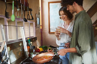 Buy stock photo Cropped shot of a young woman having wine while watching her partner cook