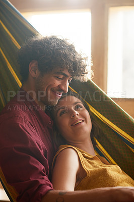 Buy stock photo Shot of an affectionate couple relaxing on a hammock at home