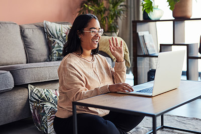 Buy stock photo Shot of a young woman using a laptop to have a video call at home