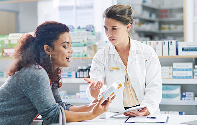 Buy stock photo Shot of a young pharmacist using a digital tablet while assisting a customer in a chemist