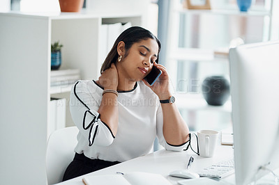 Buy stock photo Shot of a young businesswoman rubbing her neck while talking on a cellphone in an office