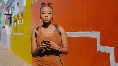 Buy stock photo Shot of an attractive young woman using a smartphone against a city background