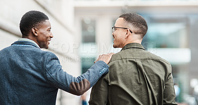 Buy stock photo Rearview shot of two young businessmen walking through the city together