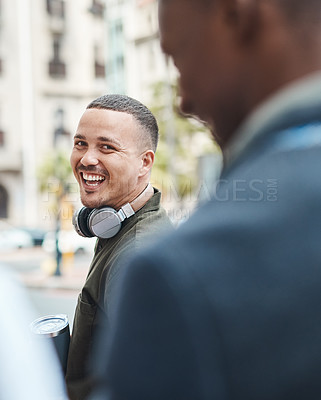 Buy stock photo Shot of a young businessman walking through the city with his colleague