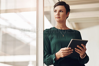 Buy stock photo Cropped shot of an attractive young businesswoman looking thoughtful while using a tablet in her office
