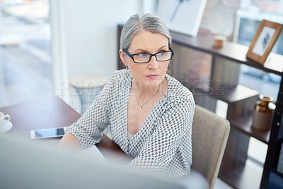 Buy stock photo Shot of a mature businesswoman looking thoughtful while working on a computer in an office