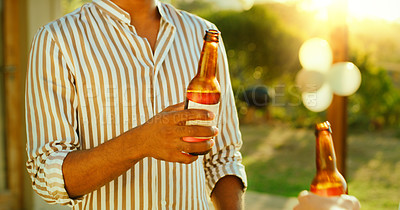 Buy stock photo Shot of two unrecognisable friends having drinks together in a garden at home