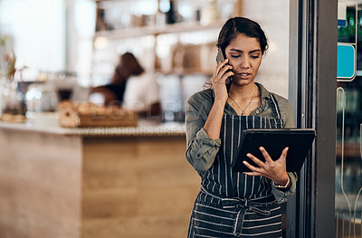 Buy stock photo Shot of a young woman using a digital tablet and smartphone while working in cafe
