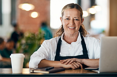 Buy stock photo Shot of a mature woman using a laptop and laptop while working in a cafe