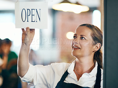 Buy stock photo Shot of a mature woman hanging up an open sign on the door of a cafe