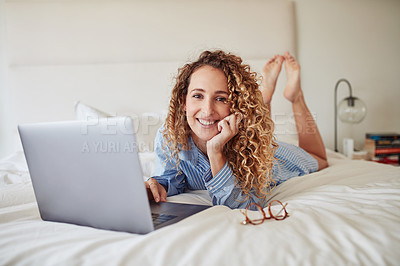 Buy stock photo Shot of a young woman using a laptop in bed at home