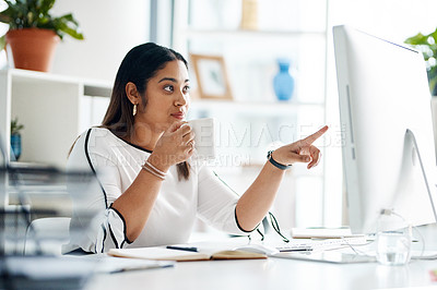 Buy stock photo Shot of a young businesswoman drinking coffee while working on a computer in an office