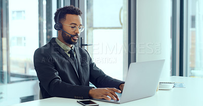 Buy stock photo Shot of a young man using a headset and laptop in a modern office