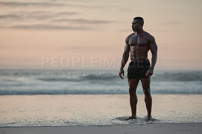 Buy stock photo Shot of a muscular young man taking a break while exercising at the beach