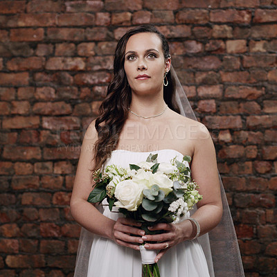 Buy stock photo Shot of a beautiful young woman holding a bouquet while standing against a brick wall on her wedding day