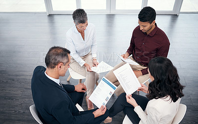 Buy stock photo Shot of a group of businesspeople going over paperwork during a meeting in a modern office