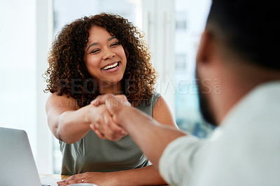 Buy stock photo Shot of a young businesswoman and businessman shaking hands during a meeting in a modern office