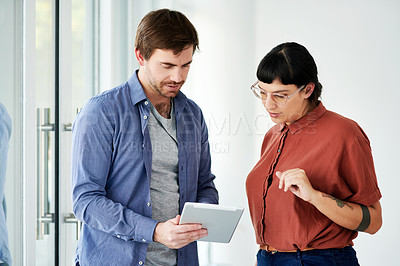 Buy stock photo Cropped shot of two businesspeople discussing something on a digital tablet