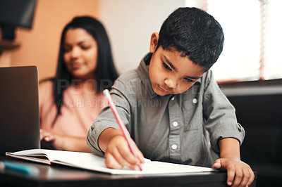 Buy stock photo Shot of an adorable little boy colouring in at home with his mother using a laptop in the background