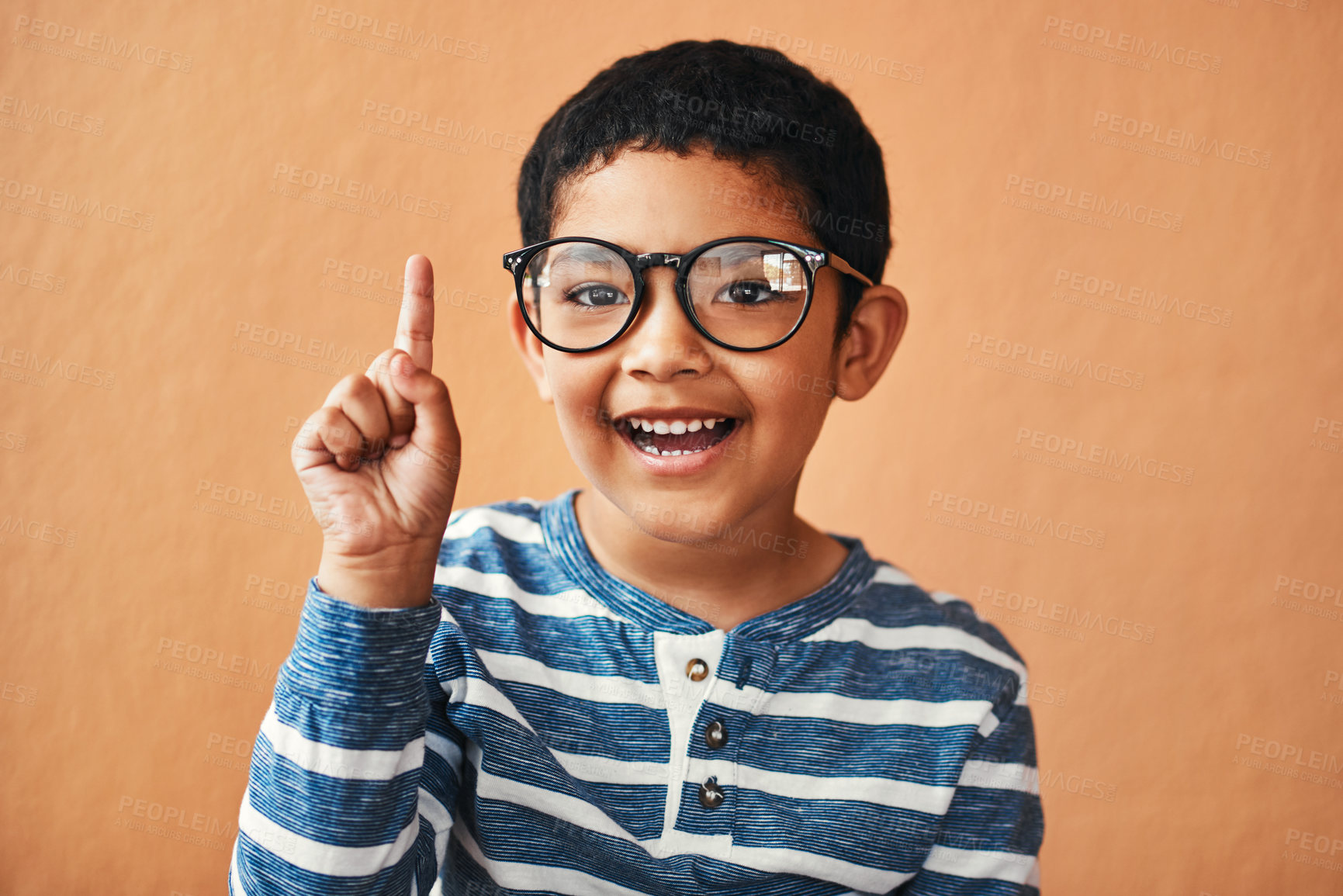 Buy stock photo Portrait of an adorable little boy wearing glasses and pointing up with his finger