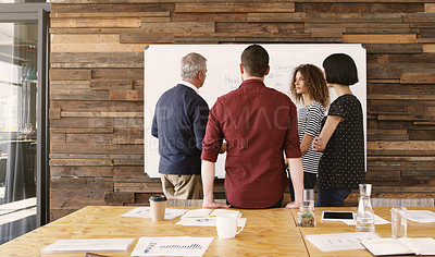 Buy stock photo Rearview shot of a group of businesspeople brainstorming with notes on a whiteboard in an office