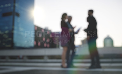 Buy stock photo Shot of a group of businesspeople having a discussion against an urban background
