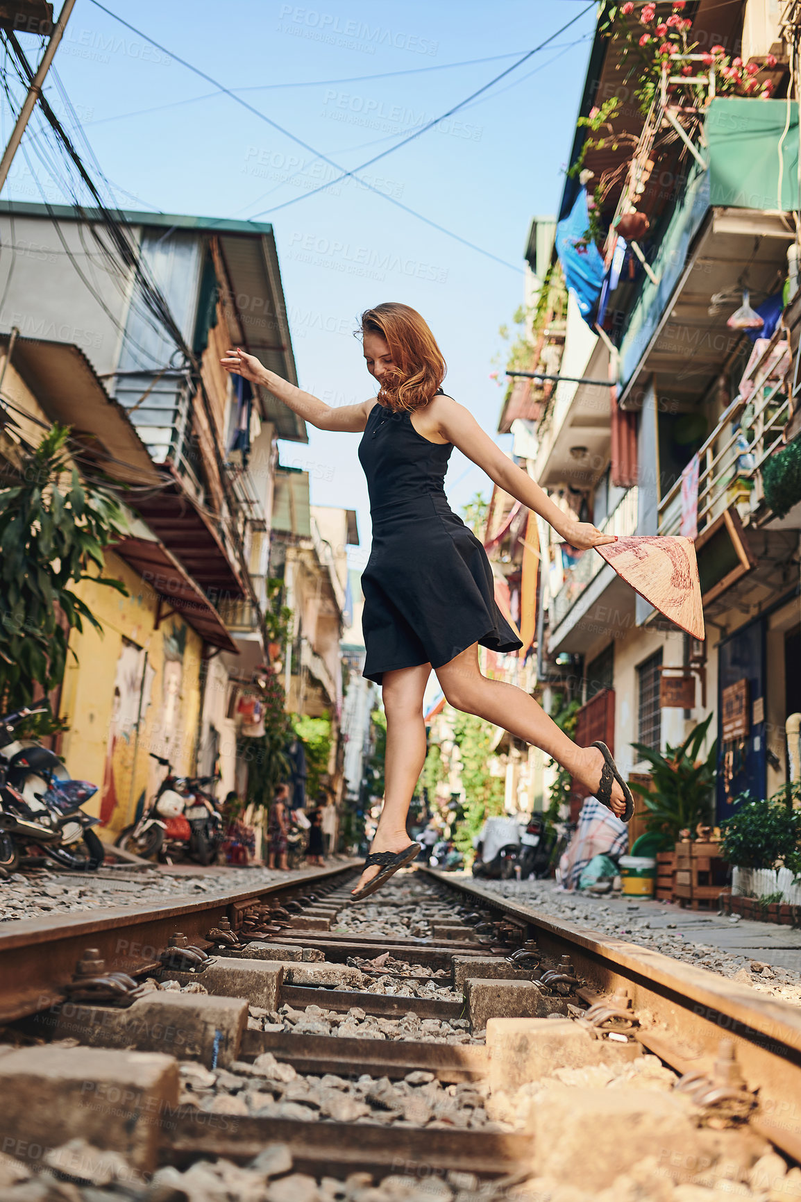 Buy stock photo Shot of a woman out on the train tracks in the streets of Vietnam