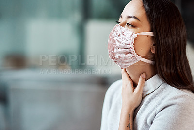 Buy stock photo Shot of a young businesswoman wearing a mask and rubbing her throat in an office