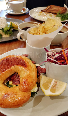 Buy stock photo Shot of a freshly made bagel served on a plate with potato crisps and a salad