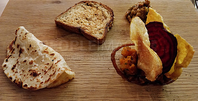 Buy stock photo Shot of a crips, bread, naan bread and a beetroot slice on a chopping board in a restaurant