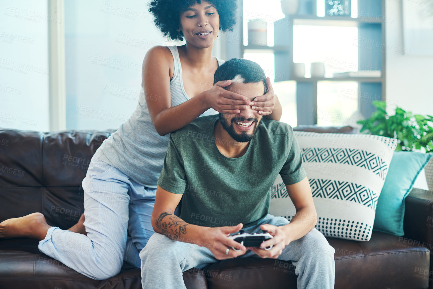Buy stock photo Shot of a woman covering her boyfriend's eyes while he plays video games