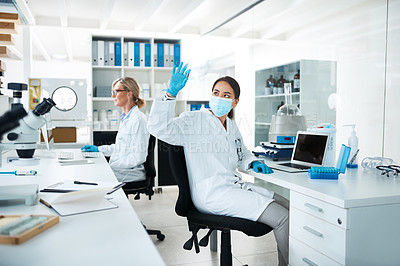 Buy stock photo Shot of a scientist analysing samples in a lab with her colleague in the background