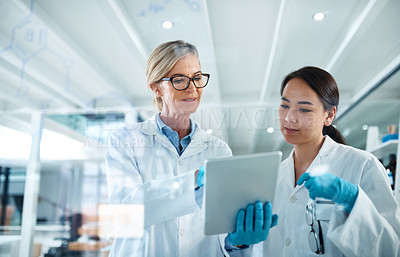 Buy stock photo Shot of two scientists working together on a digital tablet in a lab