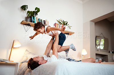 Buy stock photo Shot of a man and his son being playful before bedtime