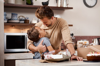 Buy stock photo Shot of a man embracing his son while celebrating his birthday at home