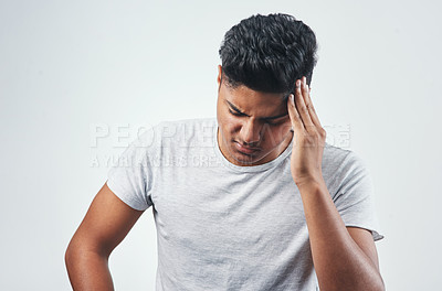 Buy stock photo Studio shot of a young man suffering from a headache while standing against a white background