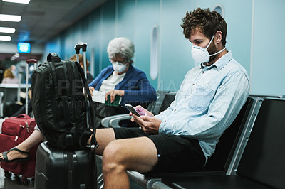 Buy stock photo Shot of a young man wearing a mask and using a smartphone in an airport waiting area