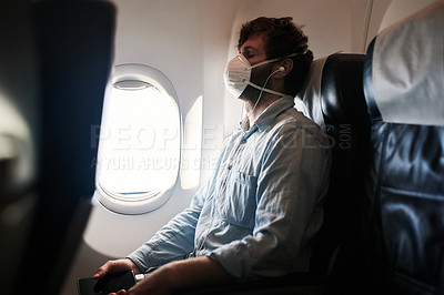 Buy stock photo Shot of a young man wearing a mask and closing his eyes while travelling on an airplane