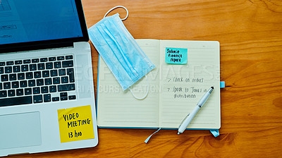 Buy stock photo High angle of a laptop, face mask and notebook on a table at home