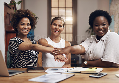 Buy stock photo Shot of a group of young businesswomen joining their hands in solidarity during a meeting in a modern office